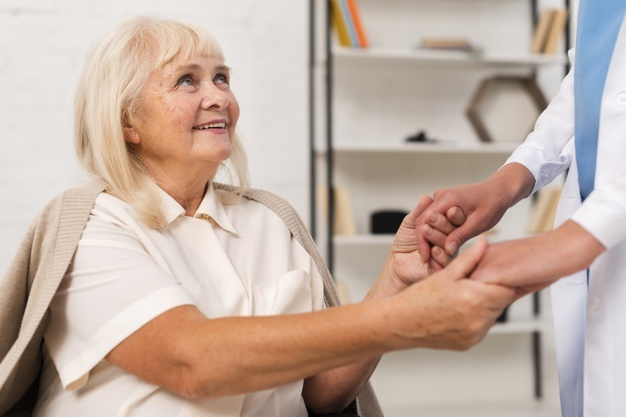 smiley-old-woman-holding-hands-with-nurse_23-2148239091